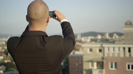 vendedor : SLOW MOTION CLOSE UP, DOF: Real estate agent standing on the rooftop of skyscraper taking pictures of the buildings and apartments on the market. Businessman working on his smartphone making snapshots