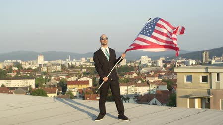 гордый : SLOW MOTION CLOSE UP: Satisfied successful businessman and patriot standing on top of tall building holding American flag proudly, celebrating success and supporting homeland, nation, culture, freedom