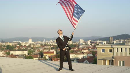 gururlu : SLOW MOTION CLOSE UP: Satisfied successful businessman and patriot standing on top of tall building holding American flag proudly, celebrating success and supporting homeland, nation, culture, freedom