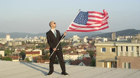 president of united states : SLOW MOTION CLOSE UP: Satisfied successful businessman and patriot standing on top of tall building holding American flag proudly, celebrating success and supporting homeland, nation, culture, freedom