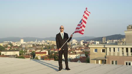 president of united states : SLOW MOTION CLOSE UP: Pleased successful businessman and patriot standing on top of tall building holding American flag proudly, celebrating success and supporting homeland, nation, culture, freedom