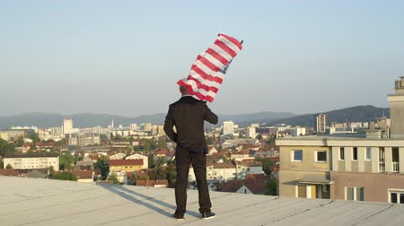 president of united states : SLOW MOTION CLOSE UP: Patriotic successful businessman standing on the edge of tall skyscraper holding American flag proudly, looking down on his home town, celebrating success and power of his nation