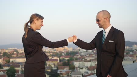 congratulating : SLOW MOTION CLOSE UP DOF: Businessman successfully accomplishing commercial deal bumping fists with female representative of corporate financial company on top of office building with stunning view Stock Footage