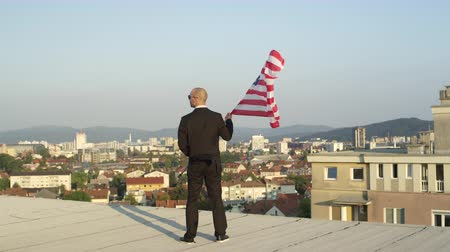 allegiance : SLOW MOTION CLOSE UP: Patriotic successful businessman standing on the edge of tall skyscraper holding American flag proudly, looking down on his home town, celebrating success and power of his nation