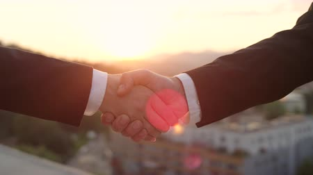 partnerstwo : SLOW MOTION CLOSE UP DOF: Unrecognizable person in formal black suit shaking hands with female co-worker when successfully concluding deal at golden sunset with beautiful cityscape in background