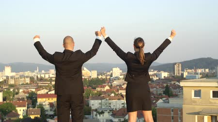erledigt : SLOW MOTION, CLOSE UP, DOF: Successful happy businessman and businesswoman standing on the edge of tall skyscraper raising hands high in the air and looking down on beautiful vivid city and green park