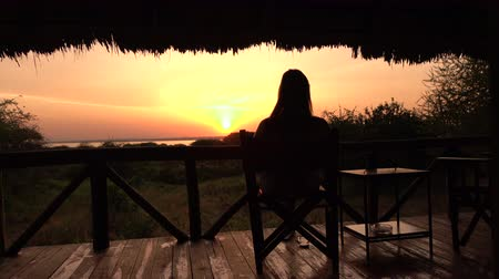 veranda : CLOSE UP: Young girl relaxing after exciting safari trip and sitting on raised wooden deck in luxury glamping hut room in Lake Burunge Tented Camp admiring bushy landscape and amazing golden sunrise