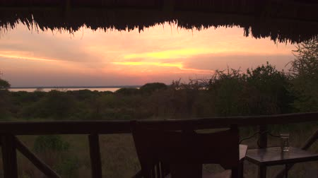sundurma : POV, CLOSE UP: Luxury lodge room apartment with raised wooden deck in glamorous tented camp with spectacular view onto Lake Burunge, lush bushland and luxuriant meadow at stunning golden light sunrise Stok Video