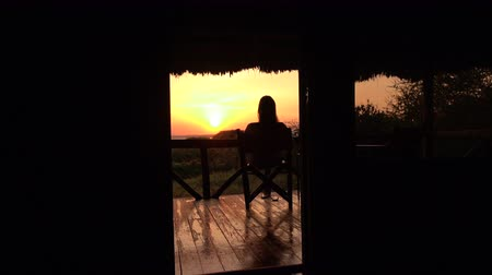 veranda : SLOW MOTION, CLOSE UP: Young girl relaxing after exciting safari trip on raised wooden deck in luxury glamping hut room in Lake Burunge Tented Camp admiring bushy landscape and amazing golden sunrise Dostupné videozáznamy