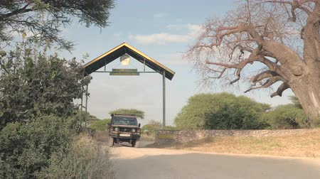 road sign : TARANGIRE, TANZANIA - JUNE 10, 2016: Park employees driving empty safari jeep and leaving wildlife Tarangire National Park to pick up new group of tourists and travelers for interesting game drive