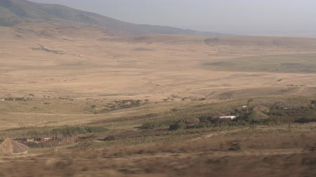 nomadic : CLOSE UP: Safari game driving past charming small Massai nomadic native tribe village with traditional circular houses built from mud, sticks and grass with beautiful overgrown mountains in background Stock Footage