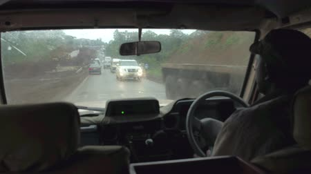 Танзания : ARUSHA, TANZANIA - JUNE 10, 2016: African guide driving safari jeep full of tourists on muddy hectic crowded local road leading through poor and filthy rural Tanzanian village on rainy bad weather day