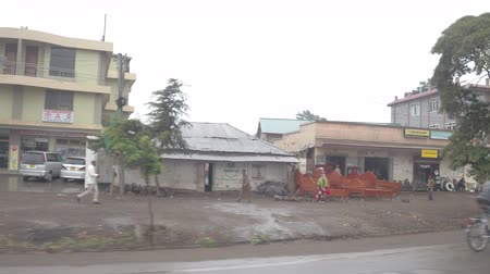 slum house : ARUSHA, TANZANIA - JUNE 10, 2016: Tourists touring in dramatic slum neighborhood driving through poor filthy decaying African city with colorful commercial markets inhabited by local village citizens Stock Footage