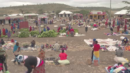 third world : KARATU, TANZANIA - JUNE 10, 2016: Flying along crowded colorful African marketplace in poor agricultural village in the city of Karatu. Local people selling shoes and bananas, sitting on the ground Stock Footage