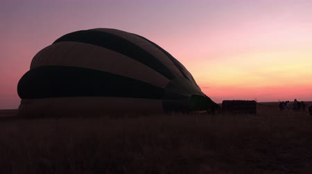 enflasyon : CLOSE UP: Preparations for ballooning adventure in stunning Serengeti. Inflating colorful safari hot air baloon lying on open short grass savannah field on early morning under pink and purple sky