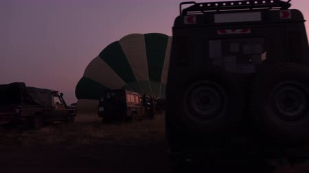 enflasyon : AERIAL, CLOSE UP: Preparations for ballooning adventure in stunning Serengeti. Inflating colorful safari hot air baloon on open short grass savannah field on early morning in rose-pink light of dawn Stok Video