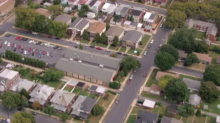 linked : AERIAL: Flying above colorful rooftops and empty streets of quiet luxury subdivision suburban town. Rows of identical twin houses, parking lots and several cars parked on the road on cloudy autumn day