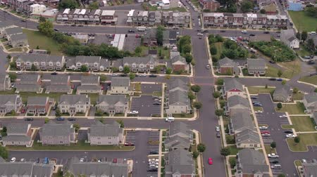 linked : AERIAL: Flying above rooftops of perfectly identical twin houses with big parking lots and colorful linked rowhouses standing along busy highway crowded with vehicles in fancy residential neighborhood Stock Footage
