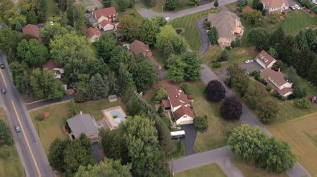 vrijstaand huis : AERIAL: Flying above rooftops of luxury suburban houses scattered around beautiful residential town. Expensive real estates with perfectly mowed lawns, swimming pools and driveway access in nature