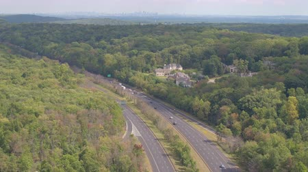 deceleration : AERIAL ESTABLISHING SHOT: Multiple lane highway leading towards New York City skyline on horizon. Semi trucks and cars driving along the busy interstate freeway past the green suburbs towards New York
