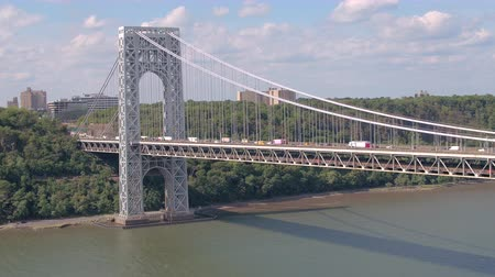 サスペンション : AERIAL: Congested traffic on the busiest suspension bridge in New York leading over beautiful Hudson River. Semi trucks, trailers and cars caught in jam driving slowly on busy interstate expressway 動画素材