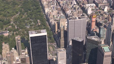 américa central : AERIAL CLOSE UP: Sunny New York city midtown Manhattan with contemporary glassy skyscrapers and condominium apartment buildings overlooking beautiful green Central park. Busy crowded NYC in America Stock Footage