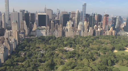 midtown manhattan : AERIAL ESTABLISHING SHOT: Flying above Central Park along 5th Avenue and towards Downtown Manhattan in sunny New York City. Tall glassy skyscrapers and condominium buildings overlooking Central Park Stock Footage