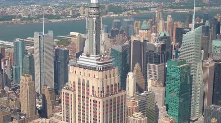 central business district : AERIAL CLOSE UP ZOOM LENS: Flying around iconic Empire State building in sunny New York city with midtown Manhattan, Hudson river and central park in the background. Helicopter flight above New York