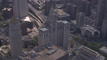 midtown : AERIAL: Flying above Manhattan Borough Presidents Office surrounded by high contemporary skyscrapers and in downtown New York City, busy traffic on a Brooklyn bridge highway in the background Stock Footage
