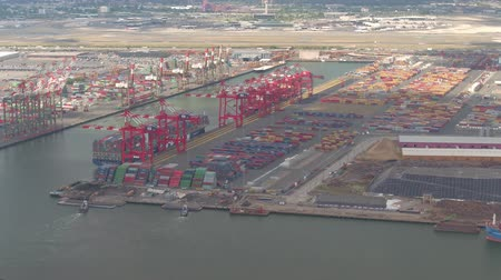 container terminal : AERIAL: Colorful containers in large trade and transportation freight harbor in sea port of New York City. Ships, vessels, boats and freighters loading - unloading cargo shipments for import - export Stock Footage