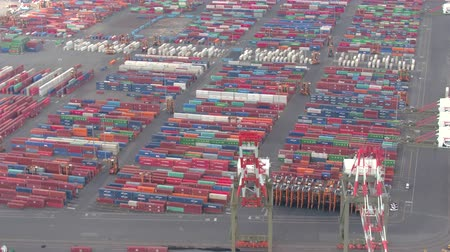 átadó : NEW YORK USA - SEPTEMBER 23: AERIAL container stacks in maritime container terminal at Newark Port of New York and Jersey. Transshipment of heavy cargo, forklift trucks loading and unloading freight Stock mozgókép