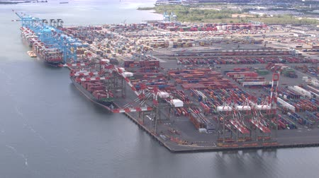 kotvící : AERIAL: Colorful freight containers in large trade and transportation harbor in sea port of New York City. Big steel cranes loading heavy cargo shipment for export on large anchored freighter ships