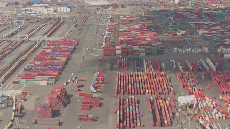 átadó : AERIAL, CLOSE UP: Colorful container stacks at maritime Port Elizabeth Terminal, Newark, USA. Shipment of heavy cargo, semi-trailer trucks unloading, forklift trucks loading freight