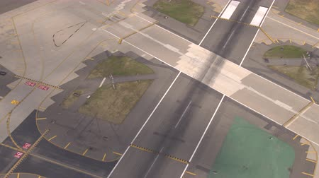 straight road : AERIAL, CLOSE UP: Flying close above large asphalt and concrete piste on big modern international airport near busy turnpike highway. Runway designator markings, numbering and signs on the track Stock Footage
