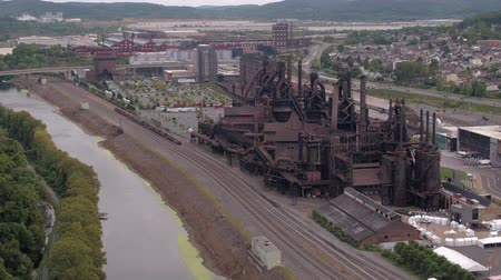 demirli : AERIAL: Flying above antique steelstacks iron works strategically placed near river current and railway road in small industrial American town in valley surrounded with overgrown lush green mountains Stok Video