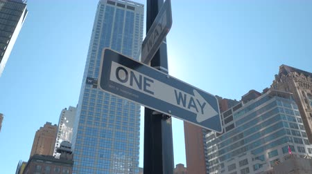 road sign : CLOSE UP, LOW ANGLE VIEW: New York City navigation indicating direction: one way road signboards fixed on a pole at traffic intersection in the downtown business district of Lower Manhattan, USA Stock Footage