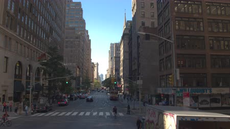 travelling : NEW YORK, Verenigde Staten - 23 september 2016: rijden langs drukke drukke 5th Avenue naar iconische Flatirion-gebouw in de zonnige stad New York. Voetganger lopen langs de straat en auto's pendelen naar het werk