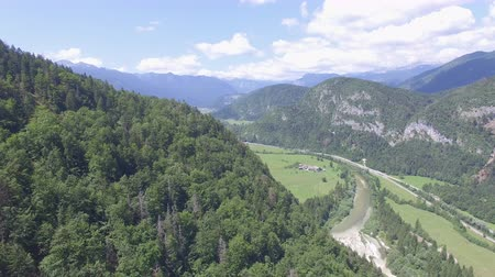 foothills : AERIAL: Flying above river meandering through green valley covered with spruce forest on sunny summer day. Winding road leading to small town on the foothills with snow-hooded mountains in background
