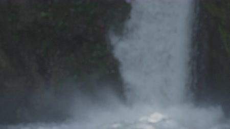 vertically : CLOSE UP, DOF: Raging whitewater waterfall cascading over steep vertical rocky wall creating small mist waterdrops floating in the air. Turbulent mountain rapids foaming when crashing on water surface