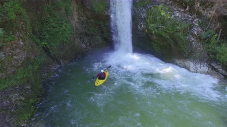 caiaque : AERIAL, CLOSE UP: Flying above extreme pro kayaker paddling against river flow towards raging whitewater waterfall cascading over rocky mountain wall and checking out the height & depth in impact zone