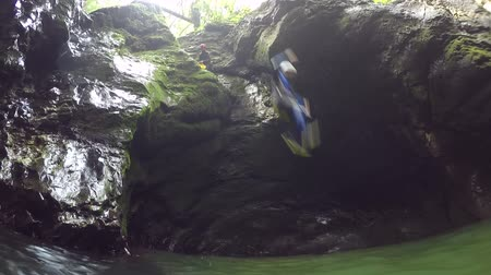 mês : FPV, CLOSE UP: Smiling active adventurous young guy on fun canyoneering experience in beautiful gorge in Slovenia, plunging off high steep rocky wall into refreshing river pool splashing waterdrops Vídeos