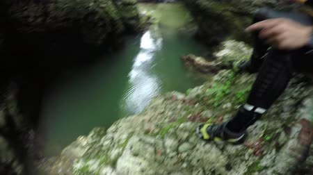 mês : POV, OVER-UNDER: Unrecognizable climber climbing mossy dangerous mountain cliff, jumping off the ledge into refreshing river pool in gorgeous ravine. Extreme adrenaline outdoor activities in nature