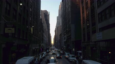 příjezdová cesta : NEW YORK, USA - SEPTEMBER 23rd 2016: Driving on small narrow street past blocks of flats, apartments and condominiums in residential area of New York City at sunset. Traffic on busy local streets