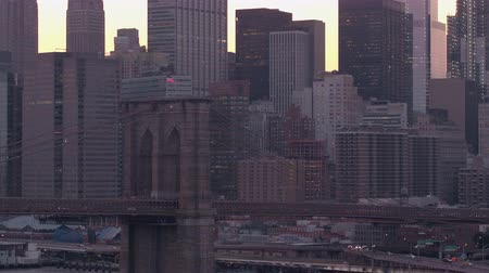 excesso de velocidade : Driving over Manhattan bridge at beautiful pink dawn overlooking the iconic Brooklyn Bridge. Modern glassy skyscrapers in downtown Manhattan business district resplendent in golden morning hues