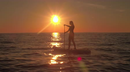 odrážející : AERIAL, CLOSE UP: Flying above pretty girl rider riding inflatable paddleboard, enjoying seaside and adventurous vacation at magical golden sunset. Sunshine reflecting on rippling sea surface