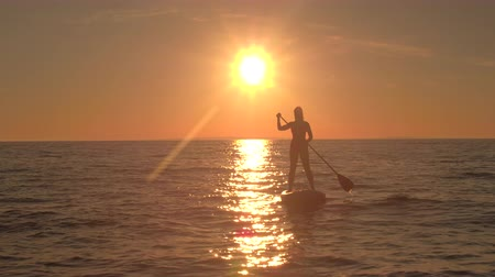 AERIAL, CLOSE UP: Flying around cheerful girl riding inflatable standup paddleboard, holding paddle and rising hands in the air. Sunshine reflecting on rippling sea surface on amazing golden sunset