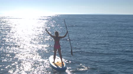 AERIAL, CLOSE UP: Flying around cheerful girl riding inflatable standup paddleboard, holding paddle and rising hands in the air. Sunshine reflecting on rippling sea surface on amazing sunny summer day