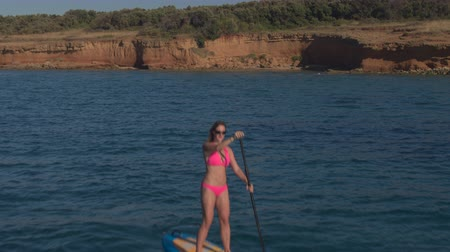 AERIAL: Flying above active woman in pink bikini surfing standup paddleboard near stunning red soil cliffy wall and pristine rocky beach overgrown with mediterranean vegetation on sunny summer day