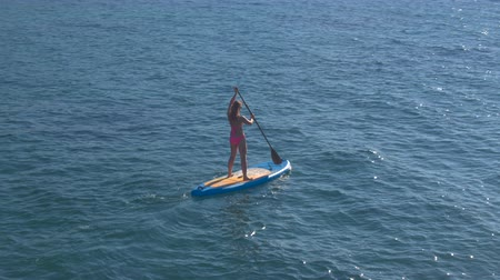 AERIAL CLOSE UP: Flying around cheerful young girl surfer riding inflatable standup paddleboard and enjoying relaxing holidays on stunning sunny summer day. Sunshine reflecting on rippling sea surface