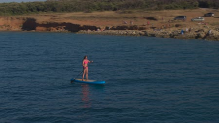 AERIAL: Flying above woman paddleboarding along stunning red soil cliffy wall and natural rocky beach on hot dry summer day. Rider in pink bikini riding SUP, holding paddle and rising hands up in air